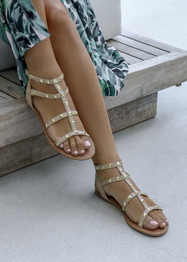 A woman's legs wearing a tropical green blue dress and Ava sandals in Nude with Gold stud details.