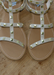 Ava sandals in Nude with Gold studded details on a wood table close up.