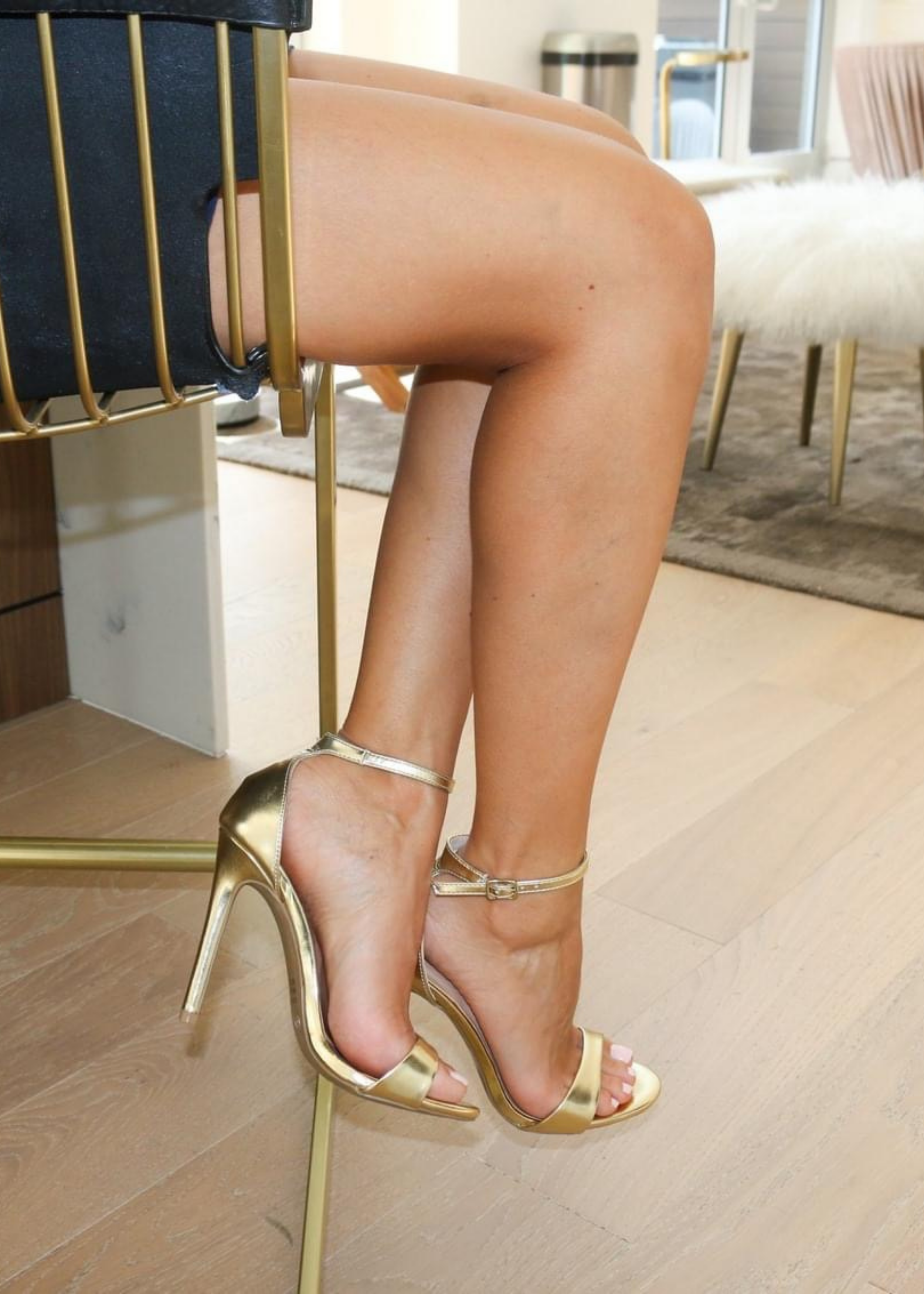 Ali Heels in gold that has a buckle on the ankle and cover heel in the back as well as thick to thin and thick again for secure and comfort .
