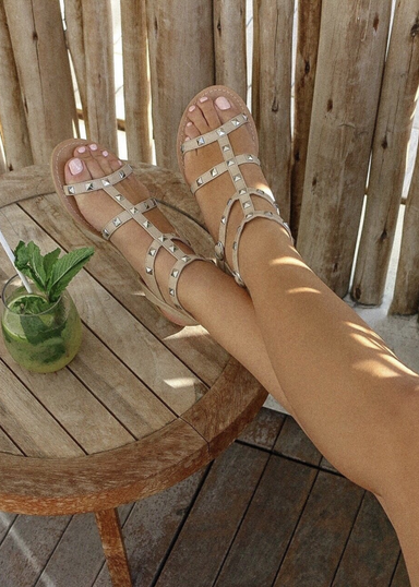 A woman's legs propped up on a side table with a tropical drink wearing Ava sandals in Nude with Silver studded details.