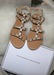 Ava sandals in Nude with Silver studded details on top of a plush fur pillow.