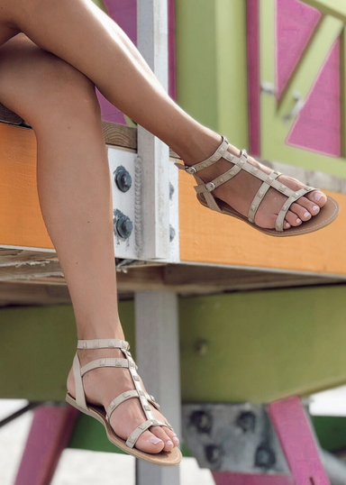 Ava gladiator sandals in nude . Model is resting her feet off of the colorful life guard station on the beach