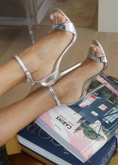 Ali Heels in Silver as the feet is propped on colorful books on a  table and candles in the back ground. It is pictured on a side view as you see buckle around the ankle. Ali Heels in Silver is a heel that is covered in the back of the heel and has a thick to thin to thick strap in the front showing your toes.