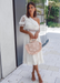 @carlanunez in ANA nude heel paired with a white dress and a blush pink top handle purse.