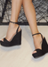 Black suede ALYSSA wedge with crisscross strap that crosses in the back as the buckle buckles in the side that is gold. Thick to thin back to thick strap in the front.