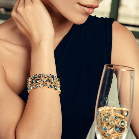 Model wearing three soft bracelets with blue stone and enjoying champagne