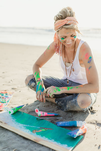 Kristina Young painting on the beach her waves