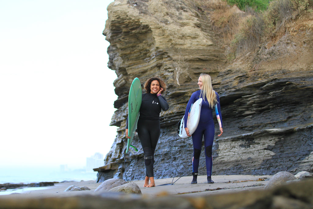 Jen and Danielle walking in baja surf her waves