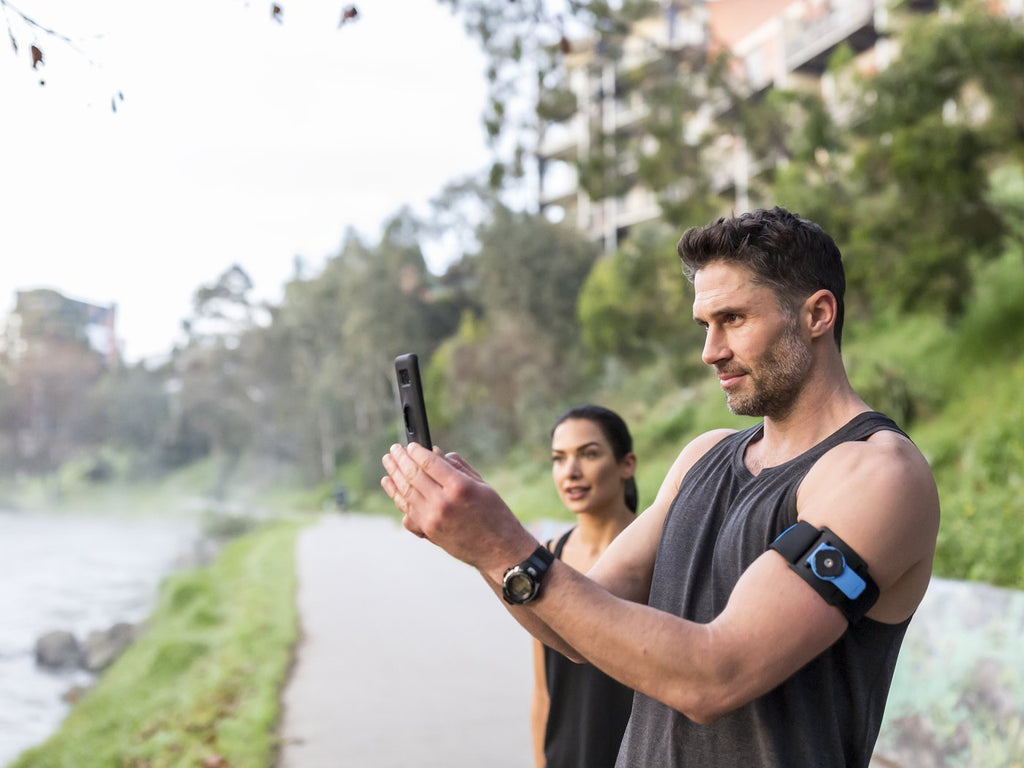 runners stop to take photo using quad lock running armband