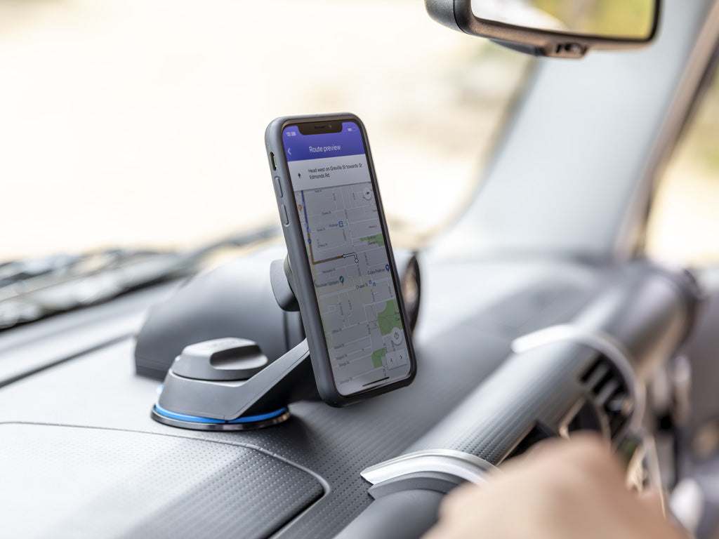 iphone attached to car mount on dash pad