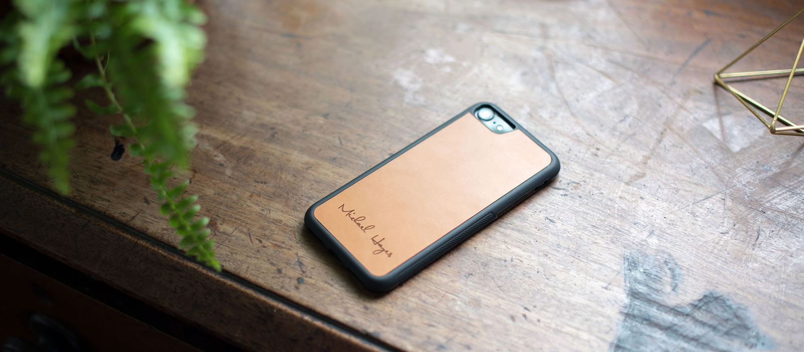 personalized leather iPhone Case on table with graphic