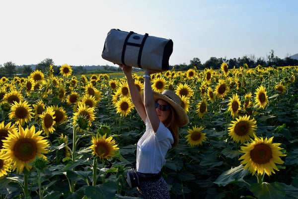 Vocco's Mediterraneo Weekender bag at a sunflowers field.
