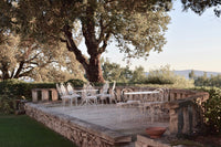 Mediterranean sunset at a beautiful stone terrace with fileds  and trees on the back. Elegant White metal chairs ant tables.