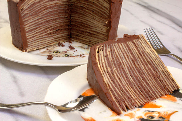 A layered crepe cake slice on a decorative plate.