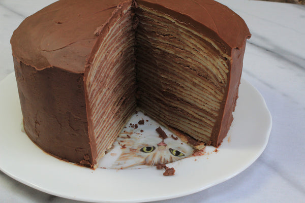 A layered crepe pancake cake displayed on a decorative plate.