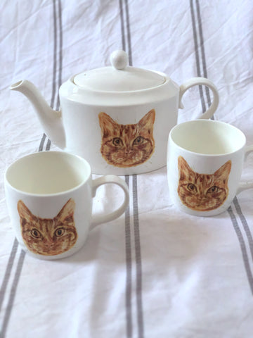 A white china tea set with illustrated pet portraits on them.