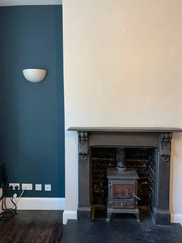 A dark indent next to a raised wall which adds depth to the fireplace.