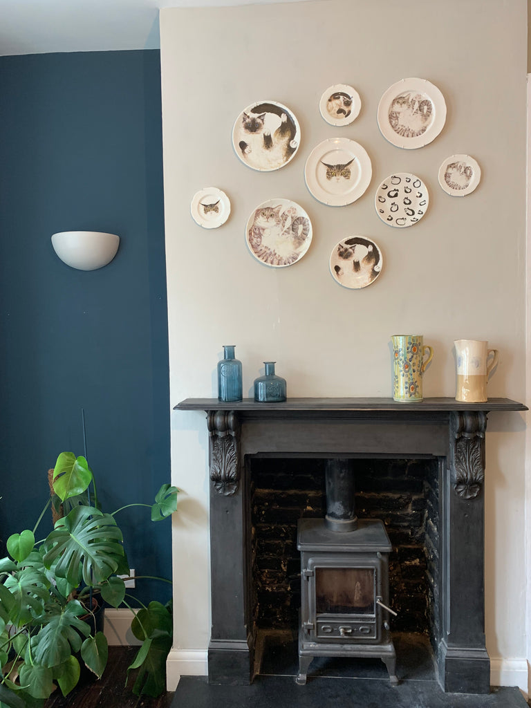 Hanging plates. Contemporary illustrated plates hung on a raised fireplace wall against Farrow and Ball Hague Blue indent.