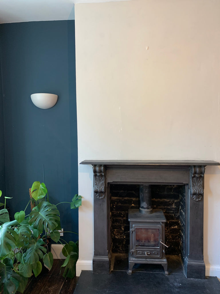 A bright raised wall with a fireplace set against a dark wall next to a cheeseplant