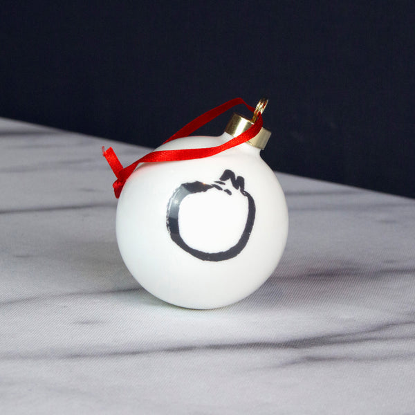 A white china bauble with a black and white cat design on it. Front view. Catnap Design London.