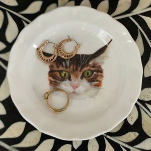 Cat face trinket dish. A white china trinket tray with a frilled edge, an illustrated tabby cat face printed on it. The cat has a very surprised expression. Aerial view of tray. Catnap Design London.