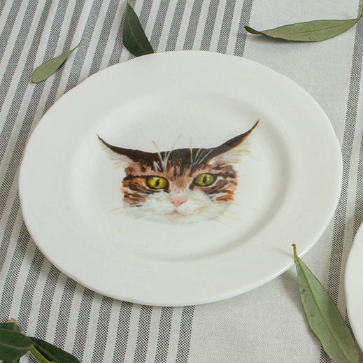 A white china plate with an illustrated tabby cat face on it. Catnap Design London.