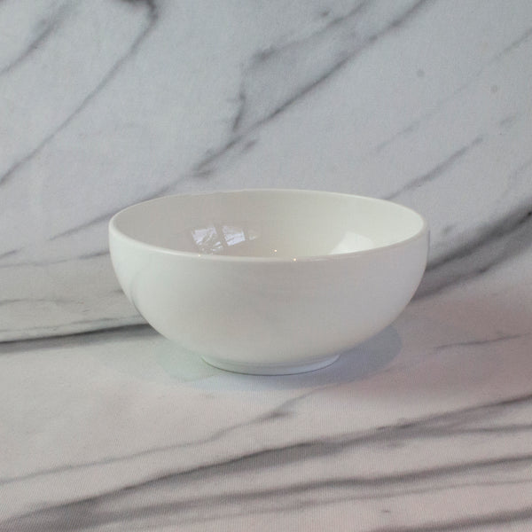 A white china cereal bowl with a tortoiseshell cat pattern in the bottom. Aerial view of bowl. Catnap Design London.