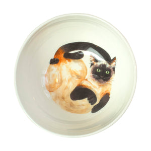 A white china cereal bowl with a Siamese cat pattern in the bottom. Aerial view of bowl. Catnap Design London.