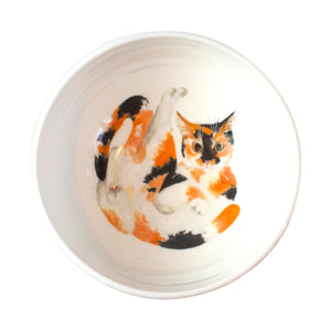 A white china cereal bowl with a calico cat pattern in the bottom. Aerial view of bowl. Catnap Design London.