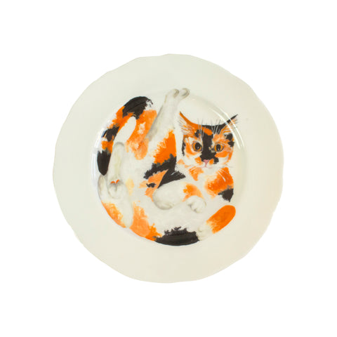 White china plates with an illustrated tortoiseshell cat printed on them. Aerial view of larger size. Catnap Design London.