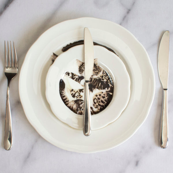 White china plates with an illustrated tabby cat printed on them. Aerial view. Catnap Design London.