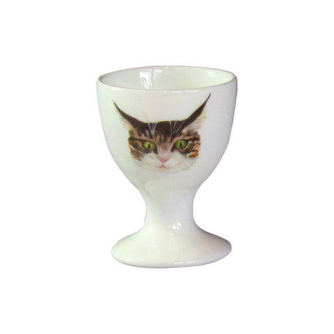 A white china egg cup with an illustrated tabby cat face on it. Catnap Design London.