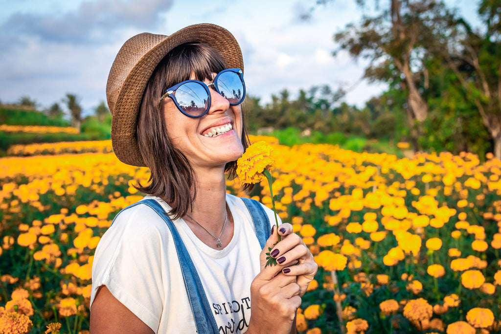 happy woman in field of yellow flowers