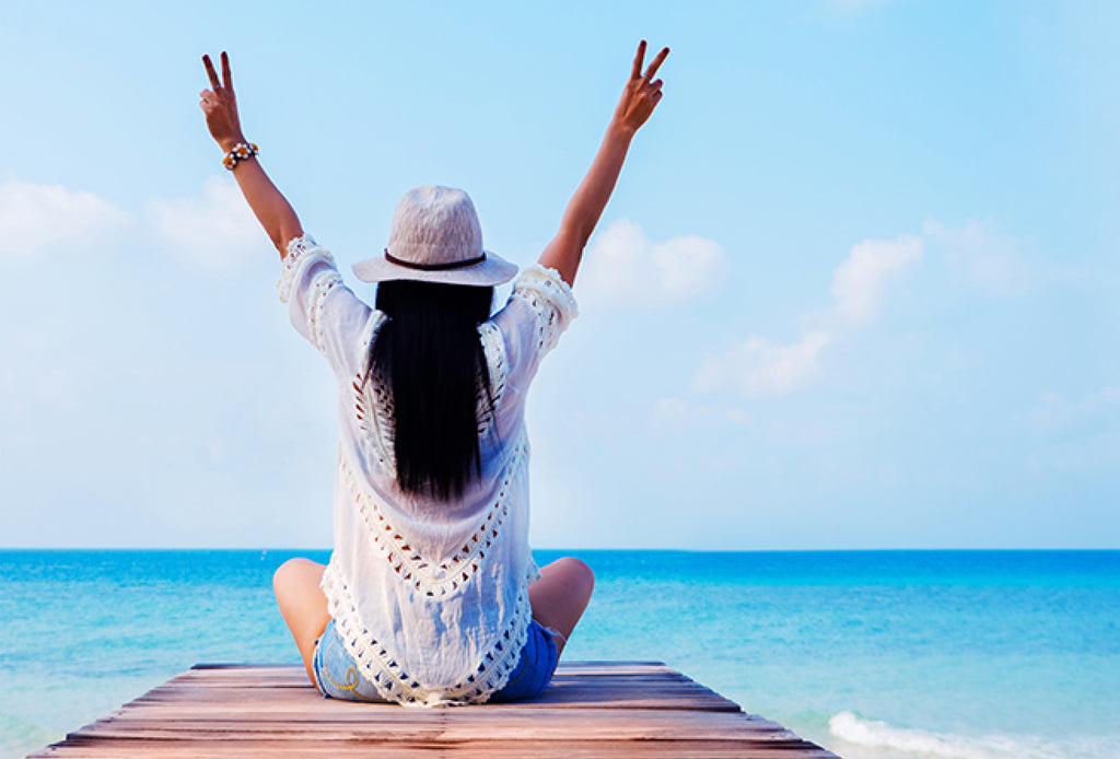 woman raising hands facing ocean