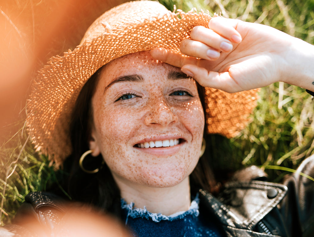 freckled woman with straw hat looking up and smiling
