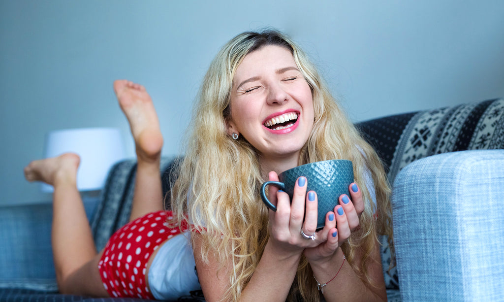 happy woman with light blue fingernails and cup