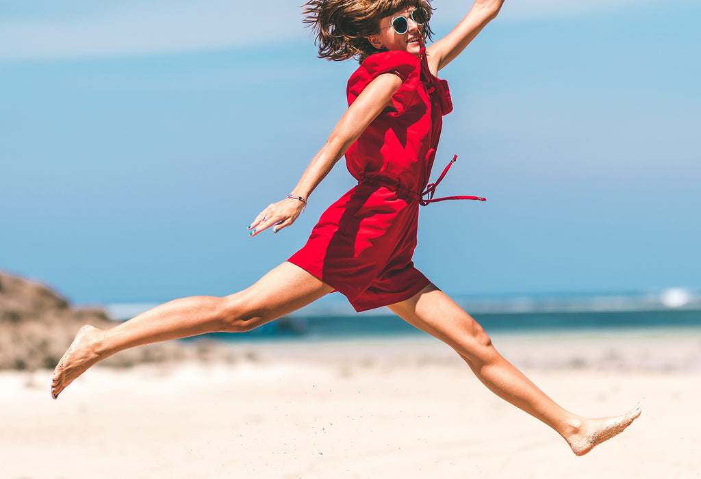 girl in red happy jumping by ocean