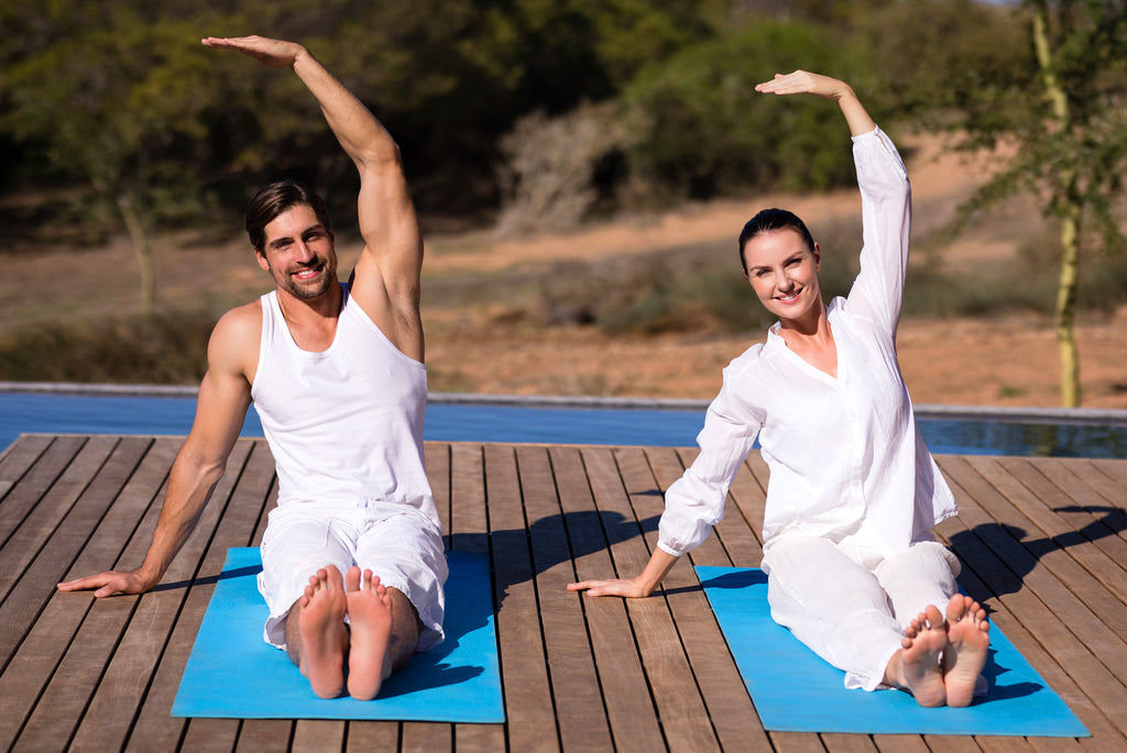 couple doing yoga by lake