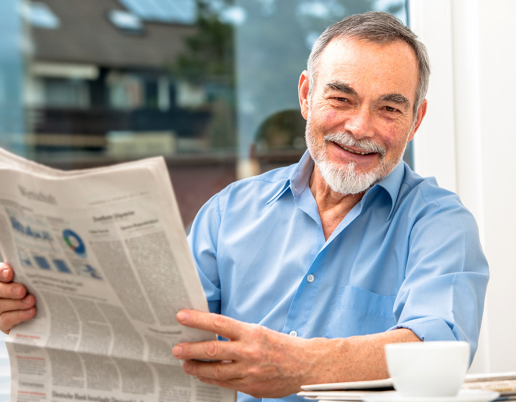 happy older man with newspaper