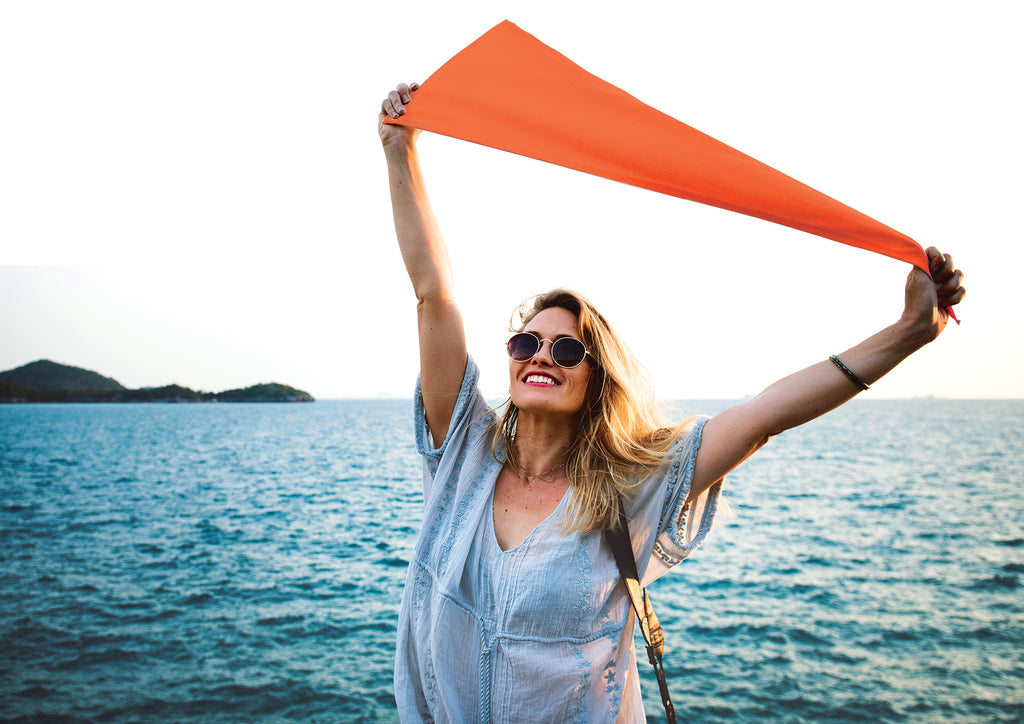 smiling woman with orange flag in front of sea