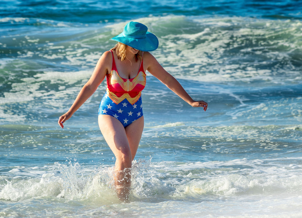 woman in red, white and blue swimsuit walks through ocean waves