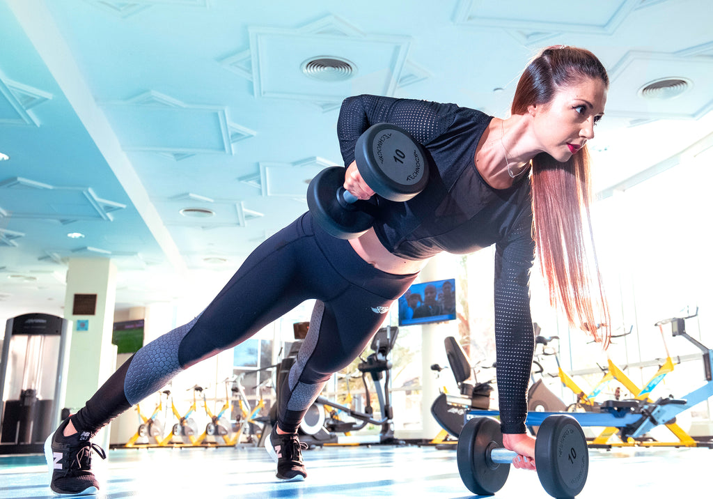 woman lifting weights off floor