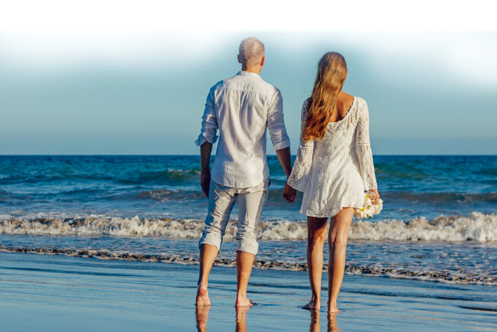 man and woman holding hands facing ocean
