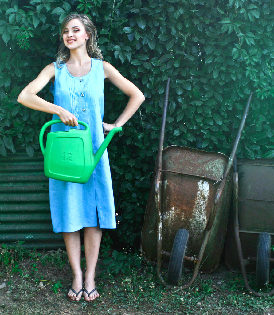 young smiling woman with watering can in front of leaf covered wall