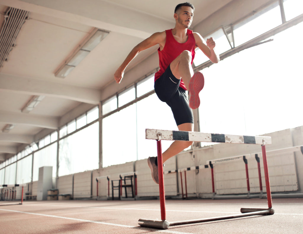 athletic man jumping over hurdle