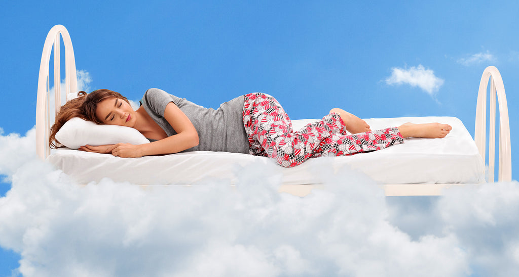 girl sleeping happily on a bed in the clouds