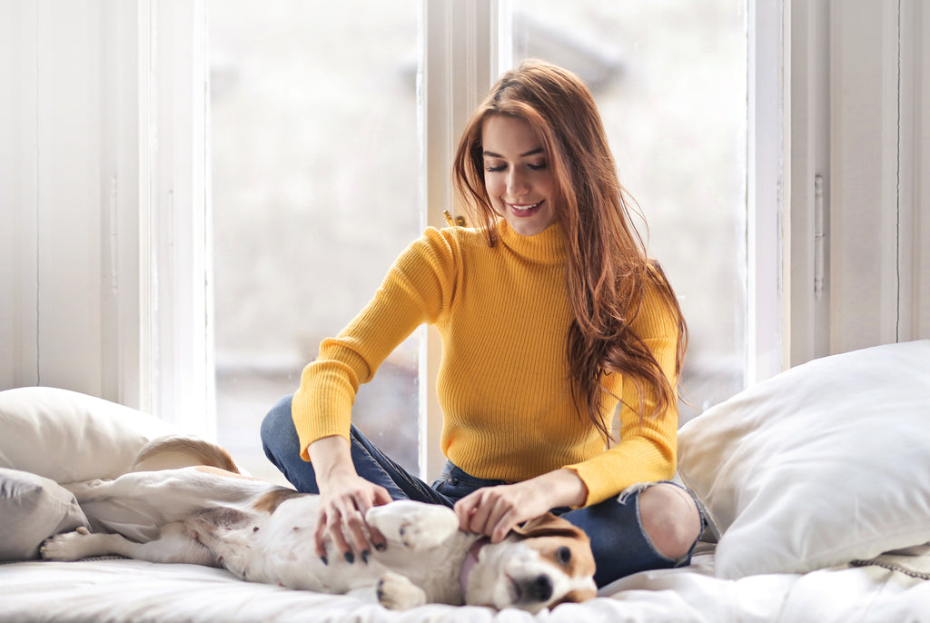 happy young woman petting dog on bed