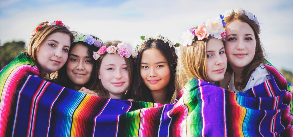 young girls with flowers in hair serape blanket