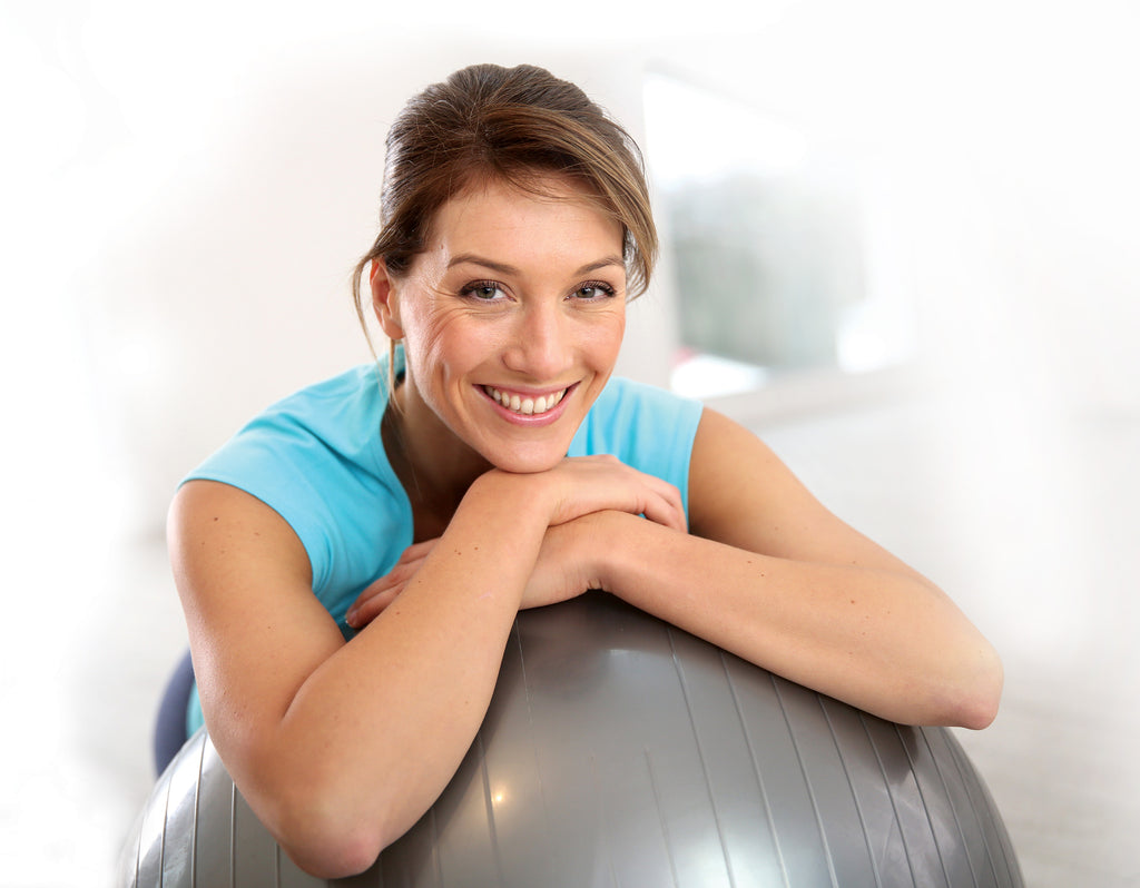smiling middle age woman leaning on yoga ball