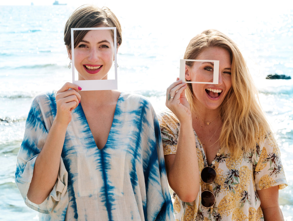 two women smiling and holding photo frame around eyes